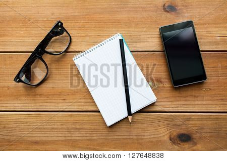 education, business and technology concept - close up of notepad with pencil, smartphone and eyeglasses on wooden table