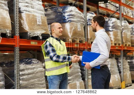 wholesale, logistic, people and export concept - manual worker and businessmen with clipboard shaking hands and making deal at warehouse