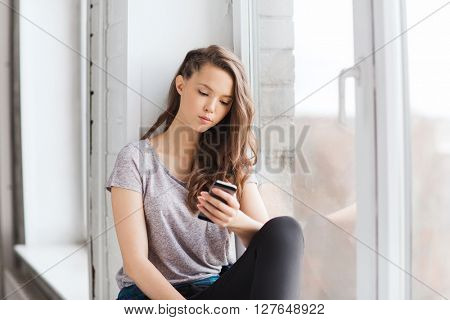 people, technology and teens concept - sad unhappy pretty teenage girl sitting on windowsill with smartphone and texting