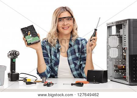 Cheerful female IT technician holding a computer part and a screwdriver isolated on white background