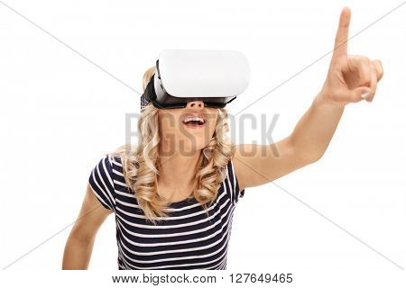 Woman using a VR goggles and reaching to touch something with her finger isolated on white background