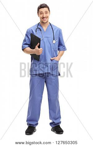 Full length portrait of a young doctor in a blue uniform holding a clipboard and smiling isolated on white background