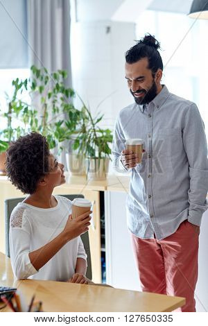 business, startup, people and drinks concept - happy latin man and african woman drinking coffee and talking in office