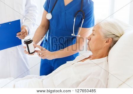 medicine, age, health care and people concept - doctor and nurse showing medicine to senior woman at hospital ward