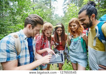 technology, travel, tourism, hike and people concept - group of smiling friends walking with backpacks and map on tablet pc computer screen looking for location in woods