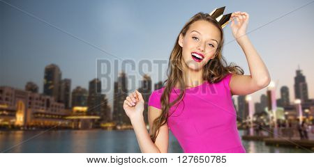 people, holidays and fashion concept - happy young woman or teen girl in pink dress and princess crown over evening city waterfront background