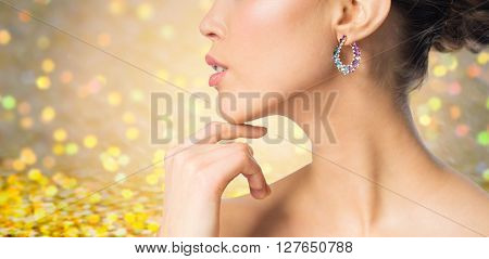 glamour, beauty, jewelry and luxury concept - close up of beautiful woman face with earring over golden holidays lights background