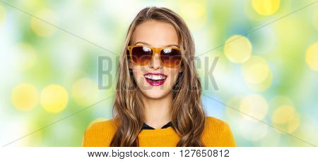 people, style and fashion concept - happy young woman or teen girl face in sunglasses over summer green lights background