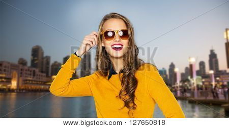people, travel, tourism, style and fashion concept - happy young woman or teen girl in casual clothes and sunglasses over evening city waterfront background