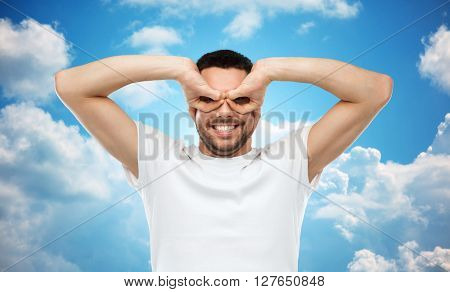 fun and people concept - man making finger glasses over blue sky and clouds background