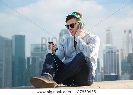 technology, travel, tourism and people concept - smiling young man or teenage boy in headphones with smartphone listening to music over singapore city skyscrapers background