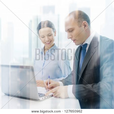 business, technology and office concept - smiling business team with laptop computer and documents having discussion in office