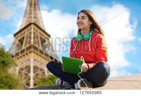technology, travel, tourism, music and people concept - smiling young woman or teenage girl with tablet pc computer and headphones over paris eiffel tower background