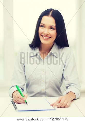 education, school and business concept - smiling businesswoman or student studying