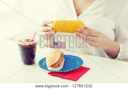 american independence day, celebration, patriotism and holidays concept - close up of woman hands holding corn with hot dog and cola drink in plastic cup on 4th july party