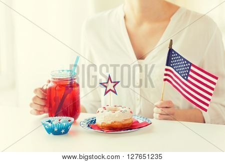independence day, celebration, patriotism and holidays concept - close up of woman eating glazed sweet donut, drinking juice from big glass mason jar or mug and celebrating 4th july at home party
