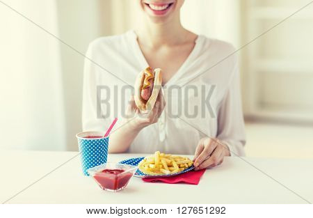 national holidays, celebration, food and patriotism concept - close up of happy woman eating hot dog and french fries with drink in paper cup at 4th july at party on american independence day