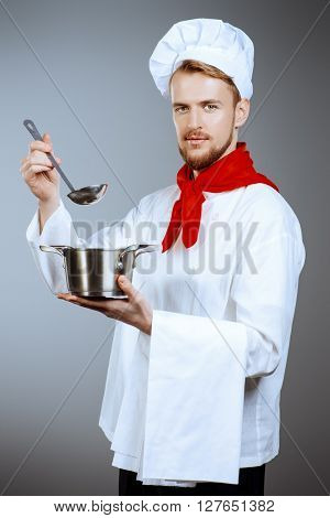 Chef tries cooked soup. Occupation. Studio shot.