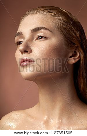 Woman With Wet Healthy Face And Hair On Brown Background