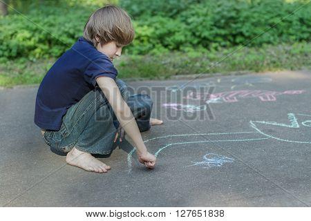 Sidewalk chalk drawings of barefoot teenage boy is wearing blue t-shirt and jeans