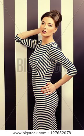 Stylish woman in elegant fitting dress and pin-up hairstyle posing at studio. Beauty, fashion concept.