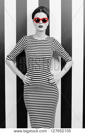 Black-and-white portrait of a fashionable lady in elegant dress and pin-up hairstyle posing at studio. Pin-up glasses, optics style. Beauty, fashion concept.