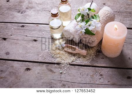 Spa or wellness setting. Beige sea salt bottles with aroma oil towels candle and flowers on white wooden background. Selective focus. Place for text.