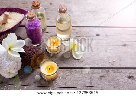Wellness or spa setting. Bottles with aroma oil sea salt towels and white plumeria flowers in ray of light on vintage wooden background. Selective focus. Place for text.