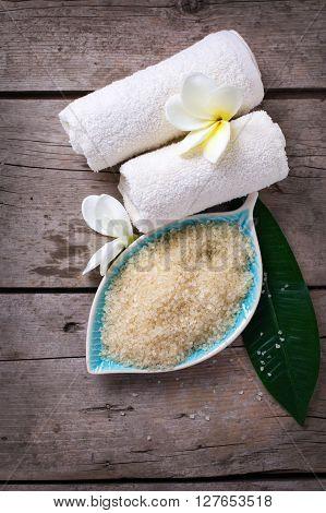 Spa setting. Sea salt in bowl in form of leaf towels on vintage wooden background. Selectivee focus.