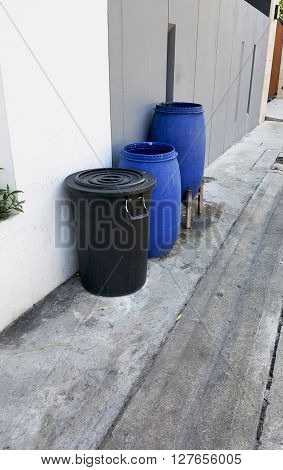Empty blue and black plastic garbage bin or trash can in front of the house