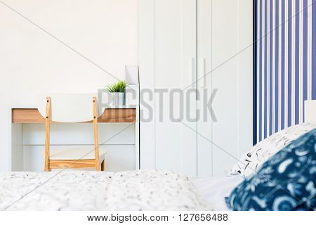 House decoration white and navy blue theme wooden desk and chair white wardrobe and vertical white/blue wallpaper.