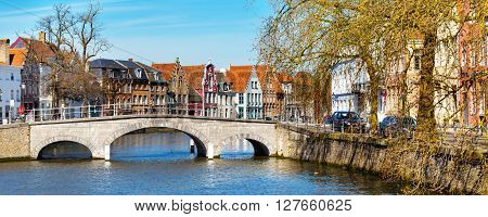 Bruges, Belgium - April 10, 2016: Panorama with canal, bridge  and colorful traditional houses against cloudy blue sky in popular belgian destination, Brugge, Belguim