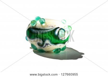 Hand made green and white glass bead on white background