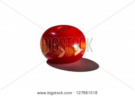 Hand made red glass bead on white background