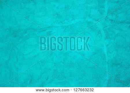 Exterior concrete wall painted in turquoise color as texture