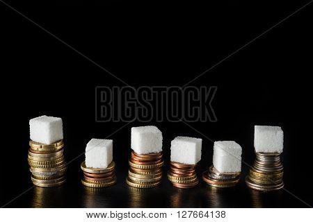 Piles of coins with sugar cubes and bottles filled with sugar on top symbolising sugar tax on black slate background