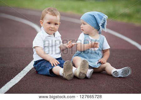 photo of little happy boy and girl on stadium