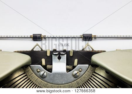 Close-up of word Risk  on typewriter sheet