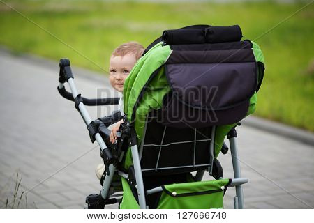 little funny boy with baby carriage outdoors