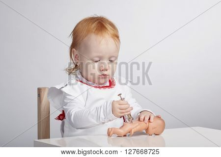 little cute girl playing doctor with doll