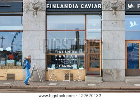 HELSINKI, FINLAND - APRIL 23, 2016: Girl walks near Finlandia Caviar Shop and Restaurant in the center of Helsinki not far from The Market Square
