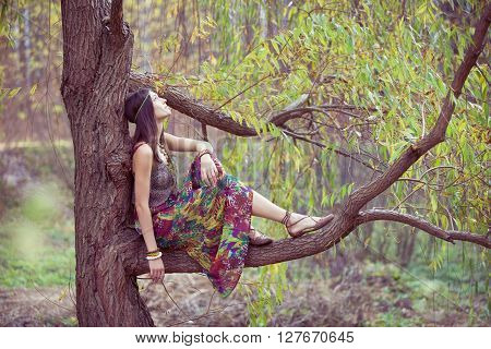 Hippie GiHippie girl on a willow tree branch