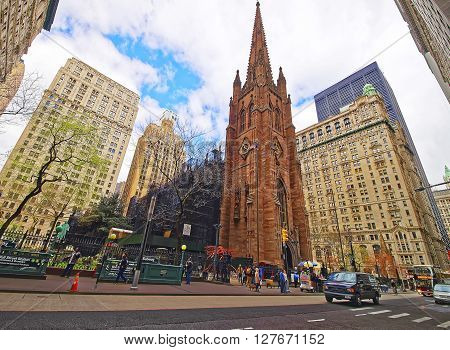 Street With Tourists And Traffic And Trinity Church In Manhattan