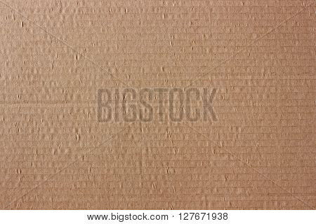 Background of the brown corrugated cardboard. Grunge texture. The sheet of corrugated cardboard closeup.