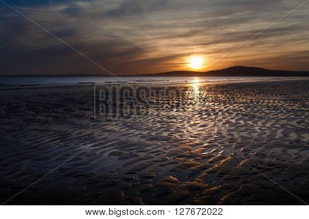 Sunset at Aberavon beach on an outgoing tide with Swansea on the horizon