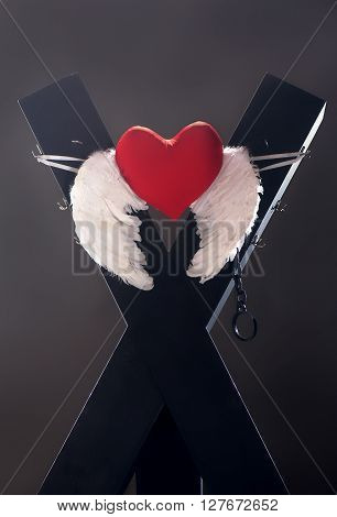 BDSM cross with white wings and red heart