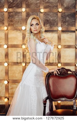 Healthy wedding hair. Attractive bride with long blonde curly hairstyle and bridal makeup standing near the brown chair on background of lightbulbs. Beauty indoor close up portrait in white dress.