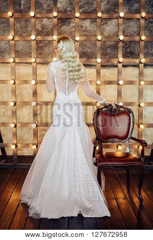 Healthy wedding hair. Attractive bride with long blonde curly hairstyle and bridal makeup standing near the brown chair on background of lightbulbs. Beauty indoor full length portrait in white dress.