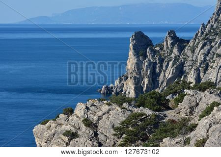 High angle scenic view towards Chicken-Kaya Cape with Main Range of Crimean Mountains and Aiu-Dag Mountain in the distance is from Koba-Kaya Mountain near New World (Novyi Svet) town Crimea Russia.