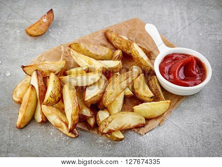 Potato wedges and tomato sauce on grey table